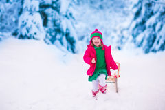 Little girl playing in snowy winter forest Stock Photography