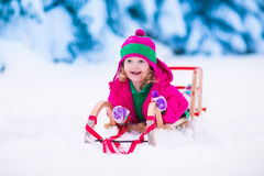 Little girl playing in snowy winter forest Stock Image