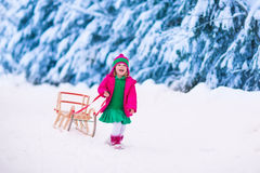 Little girl playing in snowy winter forest Stock Photos