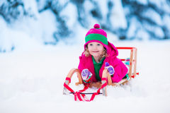 Little girl playing in snowy winter forest Stock Photo