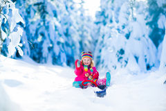Little girl playing in snowy winter forest Stock Images