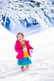 Little girl playing in snowy winter park Stock Images