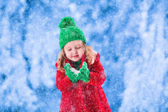 Little girl playing in snowy winter park Stock Photos