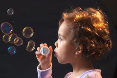 Little girl playing with soap bubbles Royalty Free Stock Photos
