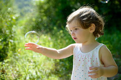 A little girl playing with soap bubbles Stock Photography