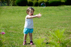 A little girl playing with soap bubbles Royalty Free Stock Image