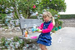 Little girl playing with soap bubbles in the garden stock photos