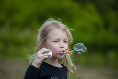 Little girl playing with soap bubbles. Royalty Free Stock Image