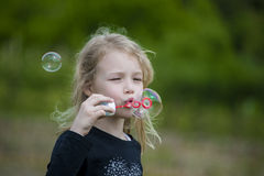 Little girl playing with soap bubbles. Stock Photos