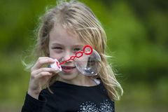 Little girl playing with soap bubbles. Royalty Free Stock Photography
