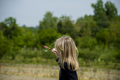 Little girl playing with soap bubbles. Stock Photo