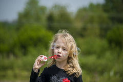 Little girl playing with soap bubbles. Royalty Free Stock Images