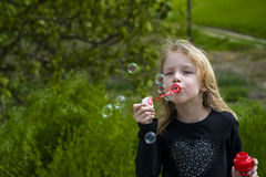 Little girl playing with soap bubbles. Stock Photography