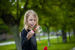 Little girl playing with soap bubbles. Stock Images