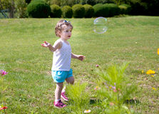 A little girl playing with soap bubbles Royalty Free Stock Photos