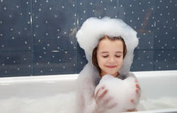 Little girl playing with soap suds  in a bath Stock Photography