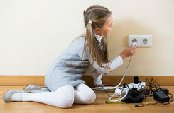 Little girl playing with sockets at home Stock Photography