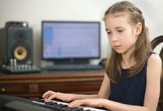 Little girl playing song on piano. Little girl playing song on piano in home music studio Stock Photography