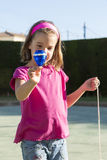 Little girl playing with a spinning top. In a playground Stock Images