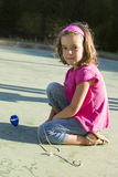 Little girl playing with a spinning top. In a playground Royalty Free Stock Photos