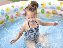 Little girl playing and spraying water in swimming pool outdoors royalty free stock photos
