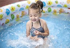 Little girl playing and spraying water in swimming pool outdoors royalty free stock image