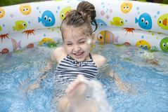 Little girl playing and spraying water in swimming pool outdoors at summer royalty free stock photos
