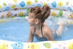 Little girl playing and spraying water in swimming pool outdoors stock photo