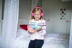 Little girl playing with spring toy with headphones Stock Images