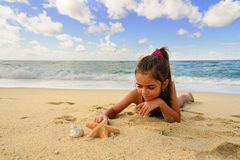 Little girl playing with a starfish on the beach Royalty Free Stock Images