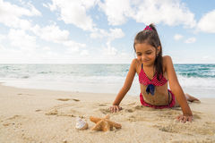 Little girl playing with a starfish on the beach Stock Images