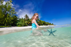 Little girl playing with starfish Royalty Free Stock Image