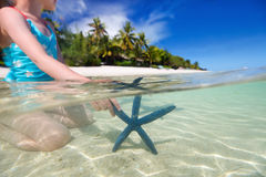 Little girl playing with starfish Royalty Free Stock Photography