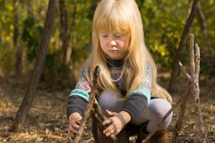 Little girl playing with sticks in woodland Stock Photos