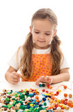 Little girl playing with string and beads Royalty Free Stock Image