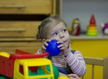 Little girl playing and studying on lessons in kindergarden royalty free stock photo