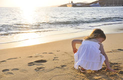 The little girl playing at sunset near the sea Royalty Free Stock Photography