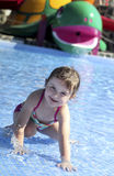 Little girl is playing in the swimming pool royalty free stock images