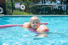 Little girl playing at the swimming pool. Cute little blonde gilr playing at the swimming pool on a summer day - childhood fun, summer vacation stock photo