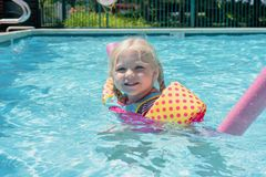 Little girl playing at the pool on a summer day. Little girl playing at the swimming pool on a hot summer day - childhood fun, summer vacation stock image
