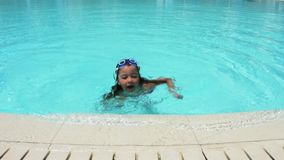 Little girl playing in swimming pool. Little girl wearing swimming glasses in swimming pool stock video