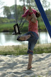 Little girl playing on a swing. Little cute happy girl playing on a swing in the sand on the beach with natural background holding the chains fast royalty free stock photography