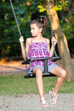 Little girl playing on the swing Stock Photography