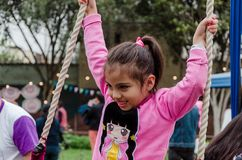 Little girl playing with the swing in the park stock photography
