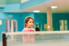 Little girl playing table tennis in the tennis hall, tennis racket hitting the ball. The pitch of the ball Royalty Free Stock Photos