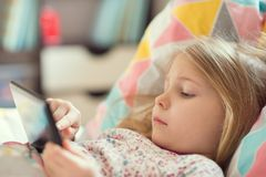 Little girl playing with tablet in bed royalty free stock images