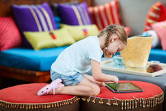 Little girl playing on tablet device Royalty Free Stock Image