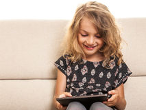 Little girl playing on tablet Royalty Free Stock Photos