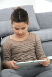 Little girl playing with tablet at home Royalty Free Stock Image