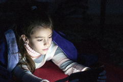 Little girl  playing tablet pc in bedroom at night Stock Photo